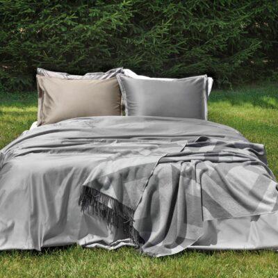 bed op gras met luxe dekbedovertrek