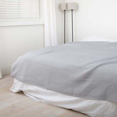 slaapkamer met houten vloer en luxe grijze bedsprei in ruitjes