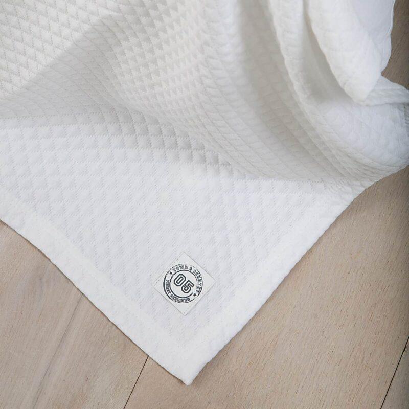 houten vloer met witte luxe bedsprei