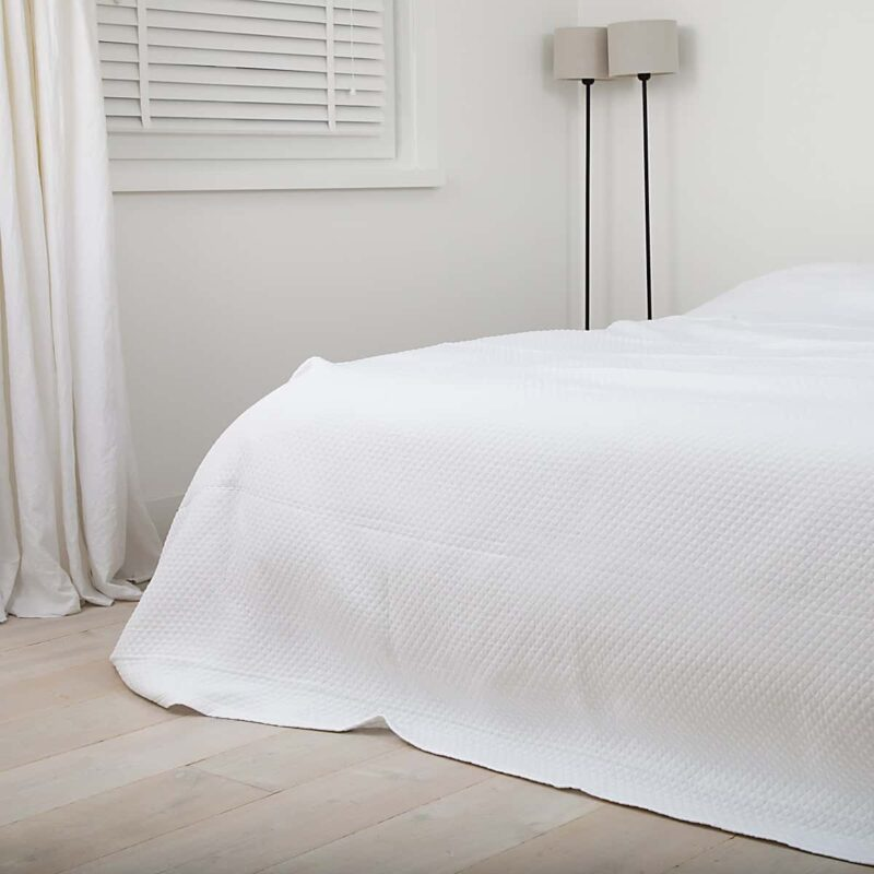 slaapkamer met wit, gordijnen, lamp en houten vloer. Bedsprei op bed is wit van kleur