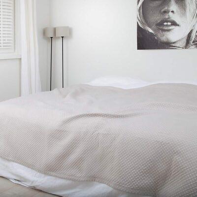 slaapkamer met schilderij, houten vloer en luxe zand kleurige bedsprei in ruitjes