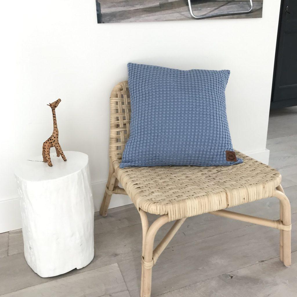 blauwe kussenhoes 50x50 op een bamboe stoel