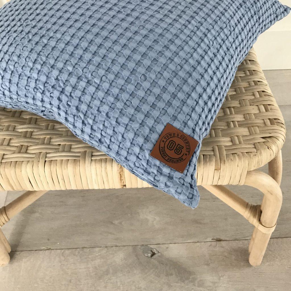 blauwe kussenhoes op een rieten stoel