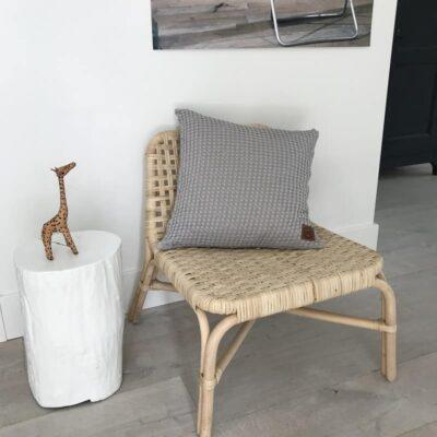 grijze kussenhoes op houten stoel met witte muren als achtergrond