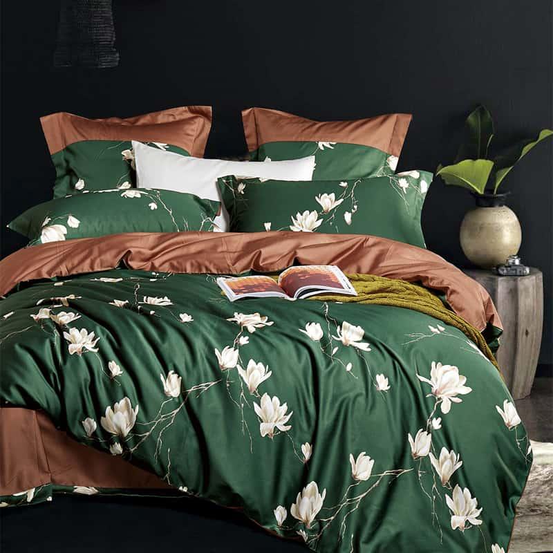bed met groen dekbedovertrek in bloemen print gemaakt van katoen satijn
