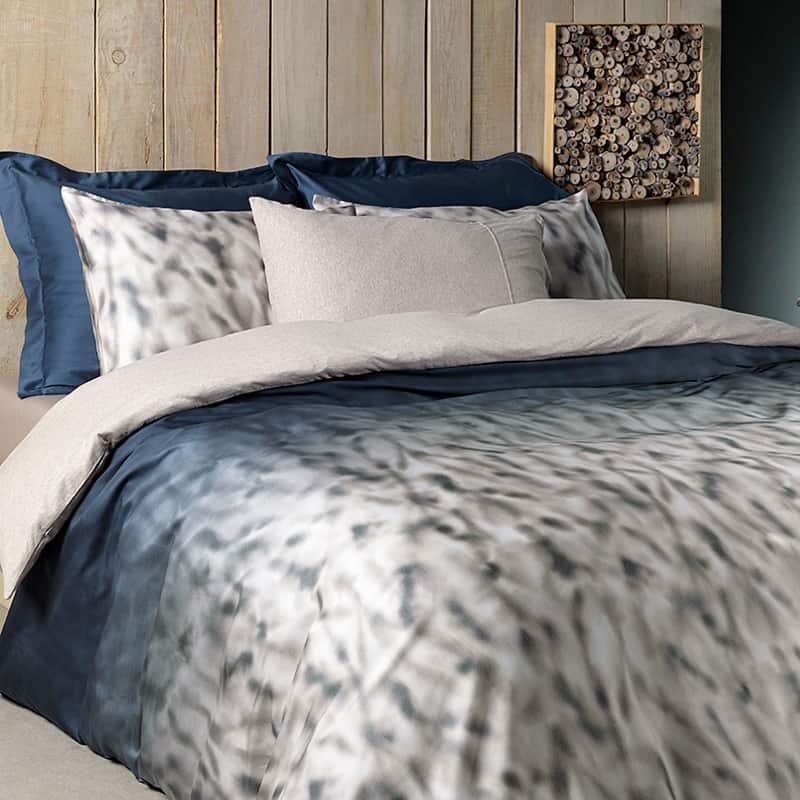 een bed opgemaakt met een blauw katoen satijnen dekbedovertrek in schaduw print