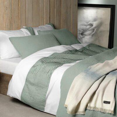 dekbedovertrek percal katoen in de kleuren wit met spargroen op een bed