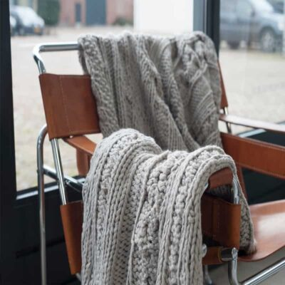 Gebreide plaid over leren stoel