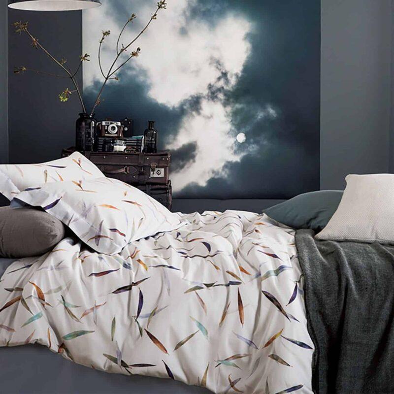 bed met wit dekbedovertrek met veertjes dessin