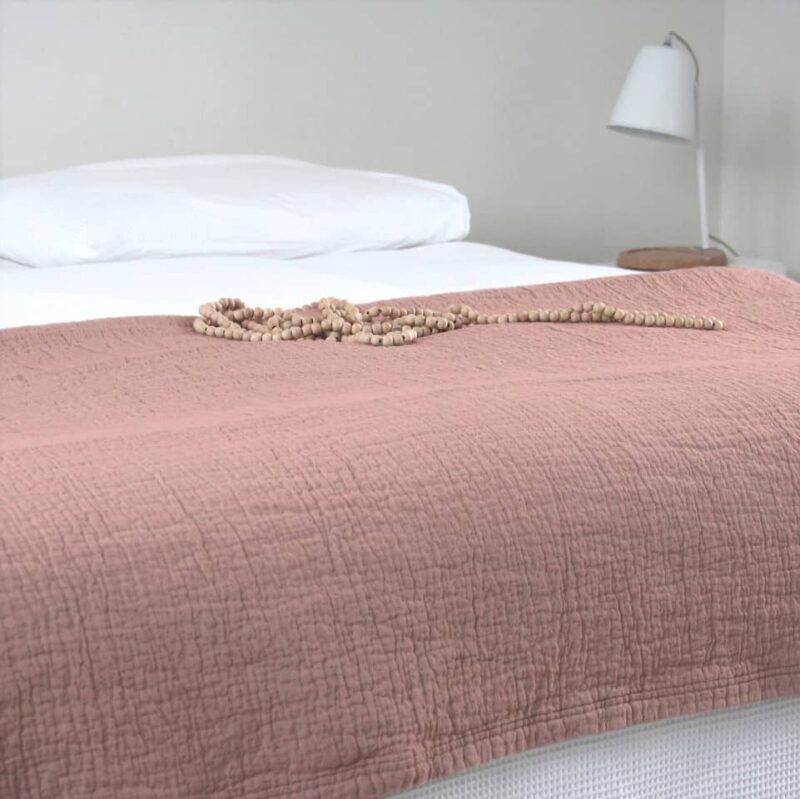 slaapkamer met wit beddengoed en oudroze sprei