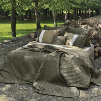 een bed buiten mooi opgemaakt in leem en brons tinten