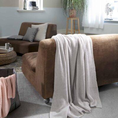 woonkamer met bruin leren bank en lichtgrijze luchtige deken in grijs
