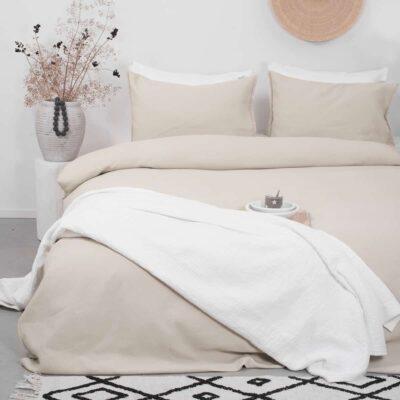 lichte slaapkamer met bed en witte sprei, wafelstructuur dekbedovertrek