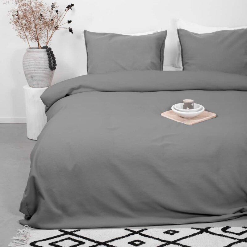 slaapkamer met plant, tapijt en grijs wafelstructuur dekbedovertrek