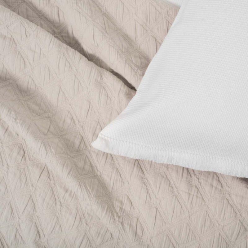 stuk van witte kussensloop en beige deken