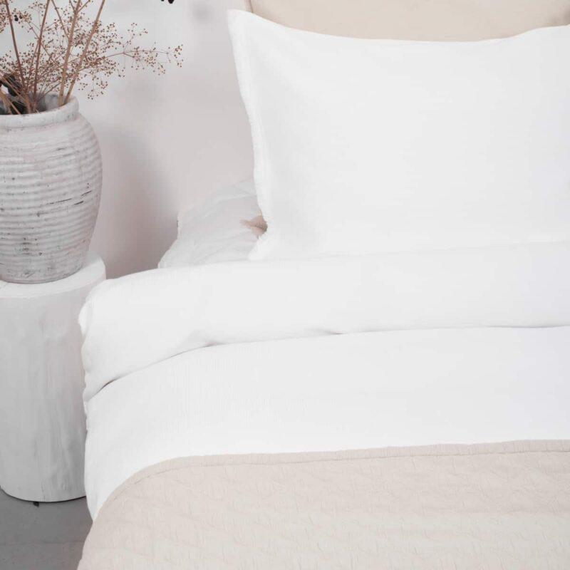 wit bed met wafelstructuur dekbedovertrek en beige bedsprei