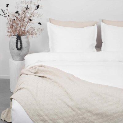 bed met sprei en wit dekbedovertrek in wafelstructuur
