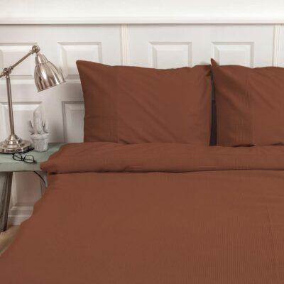 slaapkamer met terracotta gekleurd dekbedovertrek in wafelstructuur