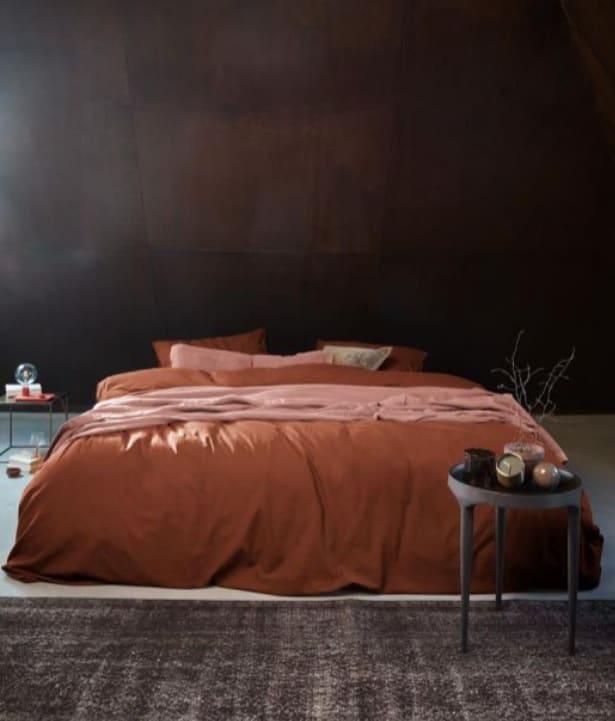 duistere slaapkamer met beton look muren en vt wonen dekbedovertrek in terracotta kleur