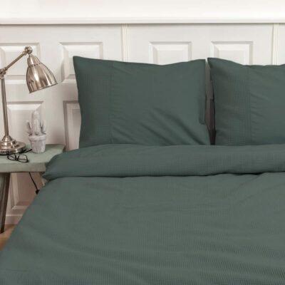 bed met donkergroen wafelstructuur dekbedovertrek en witte muren, nachtkastje en lampje