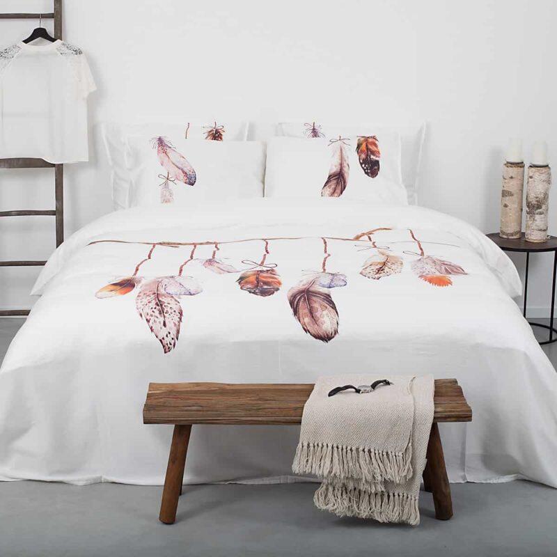 slaapkamer met wit dekbedovertrek en veren motief