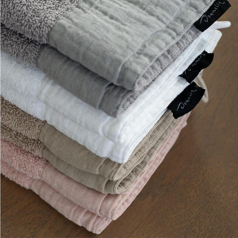 stapeltje van goede kwaliteit handdoeken in de kleuren roze, beige, wit en grijs