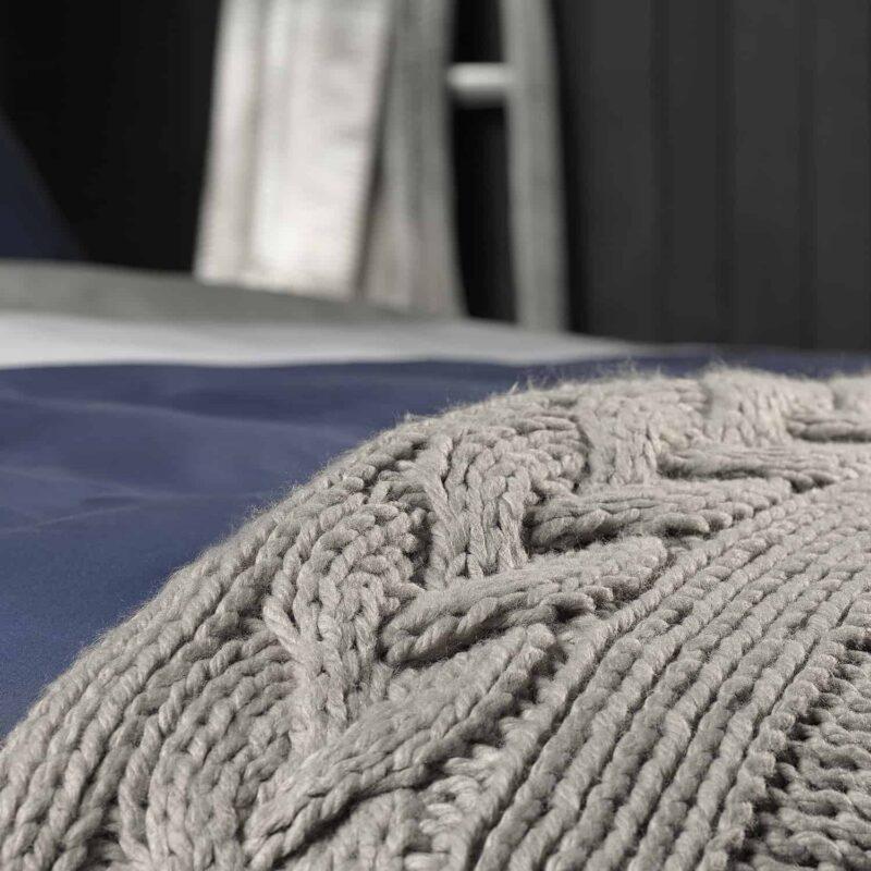 grijze plaid en stuk van een bed van dichtbij