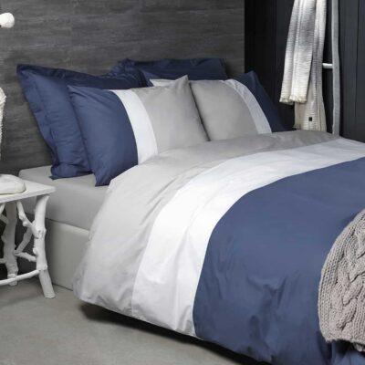 bed met grijze plaid en dekbedovertrek in blauw, wit en grijs van katoen percal