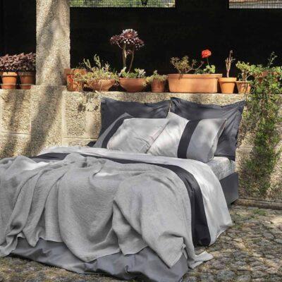 bed buiten mooi opgemaakt met een grijs percal katoen dekbedovertrek