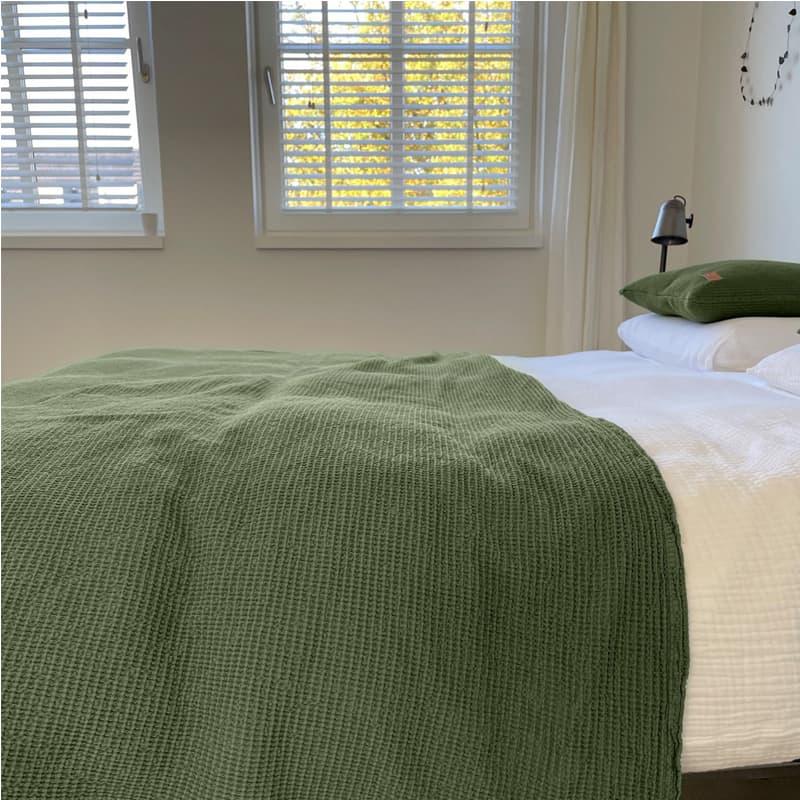 bed in slaapkamer met groene wafel sprei