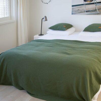 bed in slaapkamer met wit dekbed en groene wafel sprei