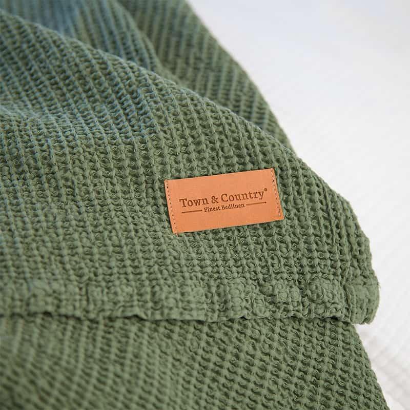 stuk stof van een legergroene sprei met wafelkatoen en bruin labeltje