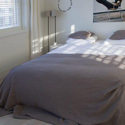 slaapkamer met een bed en lichte muren, grijze wafel sprei op het bed