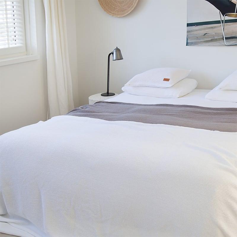 slaapkamer met een bed en lichte muren, wit wafel sprei op het bed