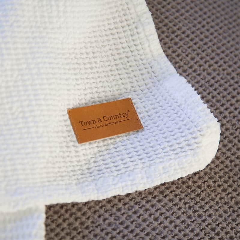 stof van witte sprei van wafel katoen met bruin labeltje