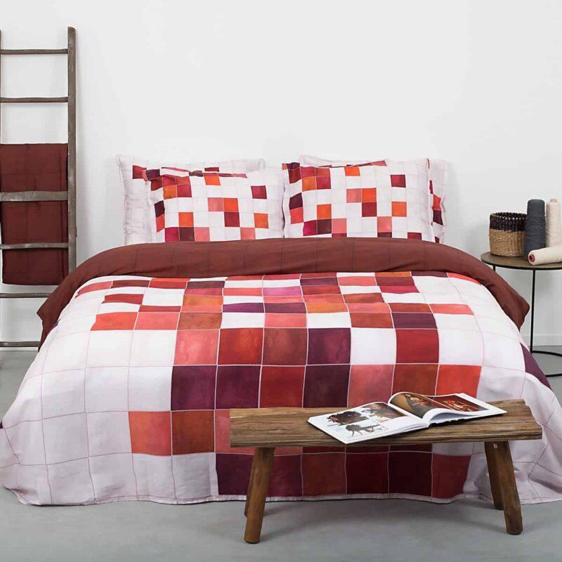 slaapkamer met grijze vloer en bed met geruit rood terracotta dekbedovertrek