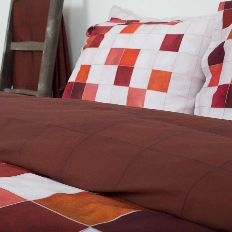 zijkant van bed met katoen satijnen dekbedovertrek in geblokte print