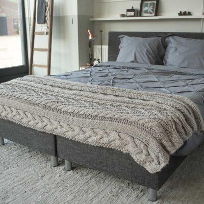 slaapkamer met bed en handgebreide sprei op grijs dekbedovertrek van katoen percal