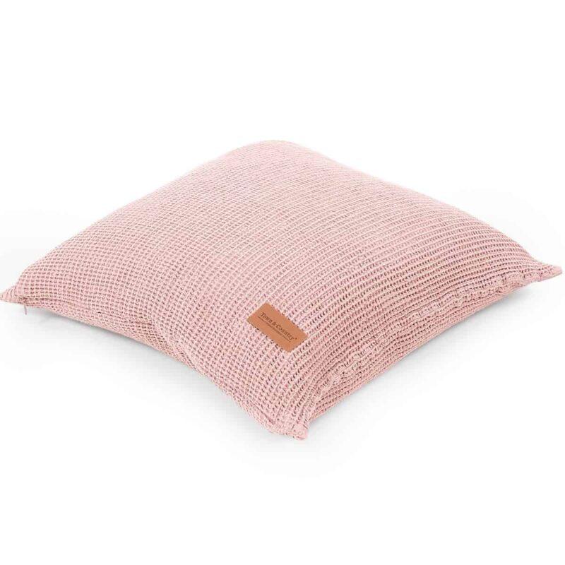 roze sierkussen van wafel stof en met een bruin leren labeltje. witte achtergrond
