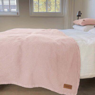 Bed met wit dekbed en licht roze wafel bedsprei