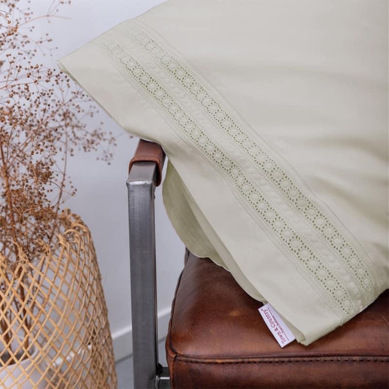 leren stoel met hoofdkussen met boderie sloop van percal katoen dekbedovertrek in beige