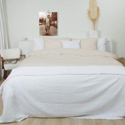 slaapkamer met bed, witte sprei en zand gekleurd katoen percal dekbedovertrek