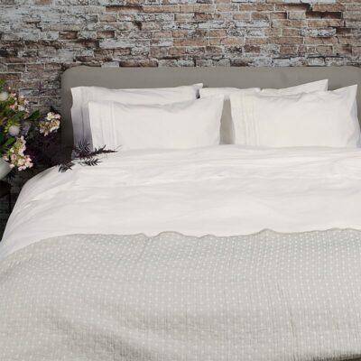 steen muur bij slaapkamer met bed en broderie dekbedovertrek in offwhite