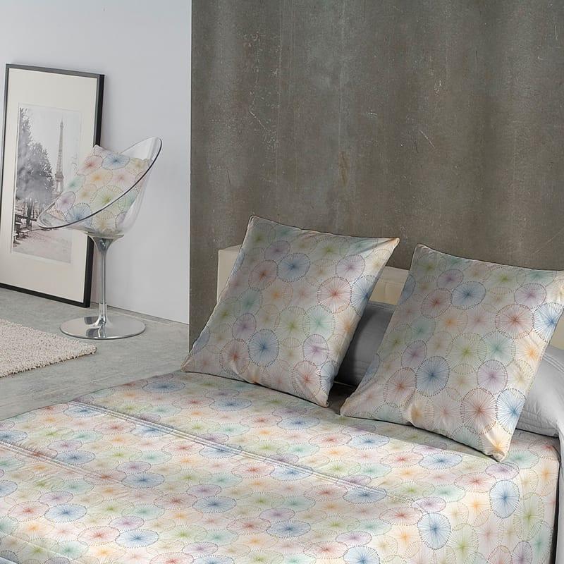 taupe muur met bed en twee kussens met kleurrijke figuren als dekbedovertrek