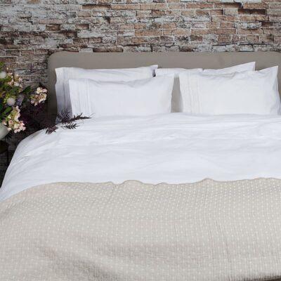stenen muur met bed en wit broderie dekbedovertrek