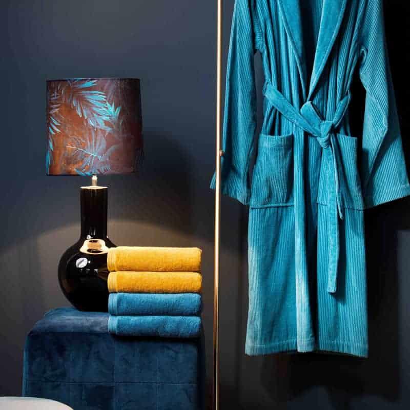 blauwe badjas en donkere muur met lamp en gele, blauwe handdoeken van merk vossen, straalt luxe uit
