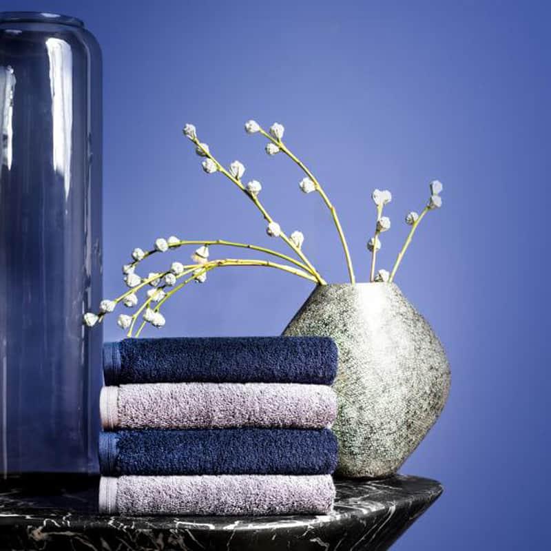 blauwe muur met vaas en stapel van 4 hotelkwaliteit handdoeken in marine blauw en grijs