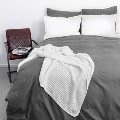 bed met stoeltje en grijs luxe dekbedovertrek met witte sprei en kussens