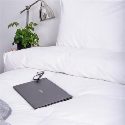 wit bed, boek en nachtlampje met luxe dekbedovertrek