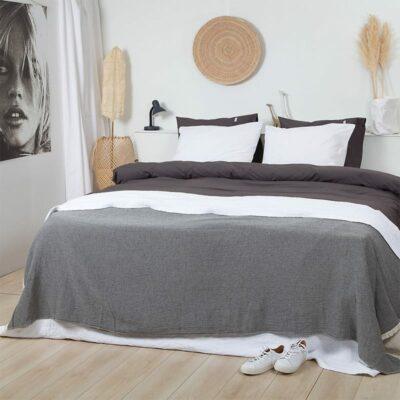 slaapkamer met bed, houten vloer. grijze bedsprei en wit met grijs percal katoen dekbedovertrek